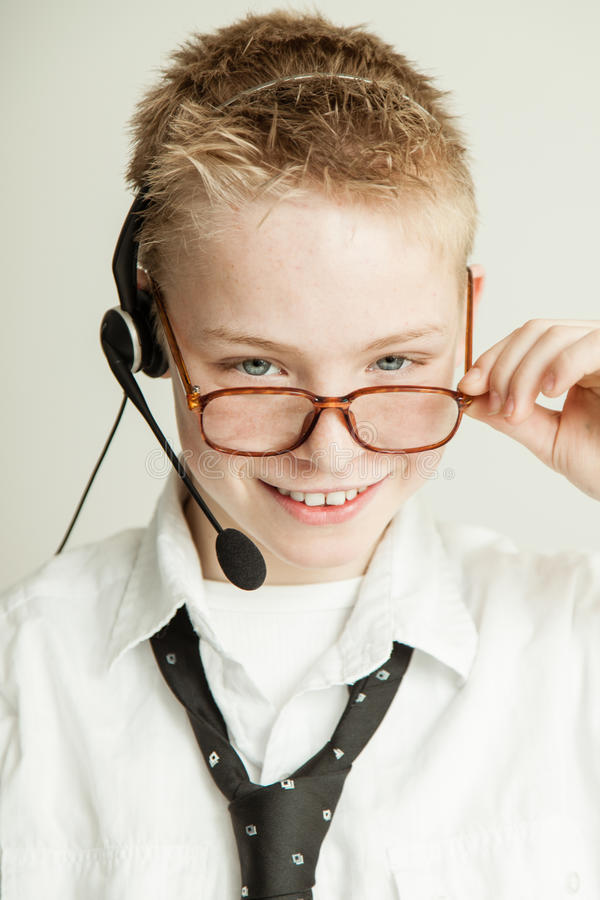Smiling Boy Dressed as Businessman with Head Set. Occupation Concept Image - Head and Shoulders Portrait of Young Blond Pre Teenage Boy with Spiked Hair Smiling stock image