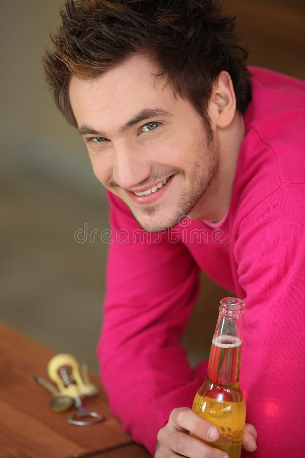 Smiling boy drinking beer royalty free stock image