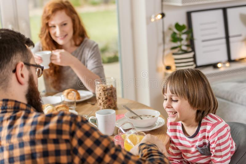 Boy eating breakfast with father. Smiling boy eating breakfast with his father and mother at home royalty free stock image