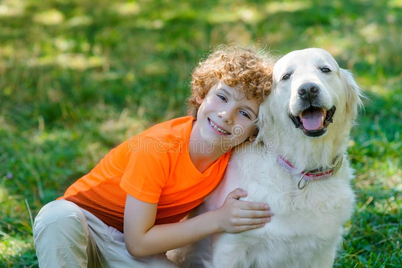 Smiling boy embraces his dog royalty free stock photography