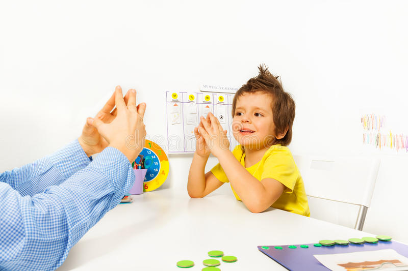 Smiling boy exercises improving motor skills. Smiling boy exercises putting hands and fingers together with therapist improving motor skills sitting opposite at stock images