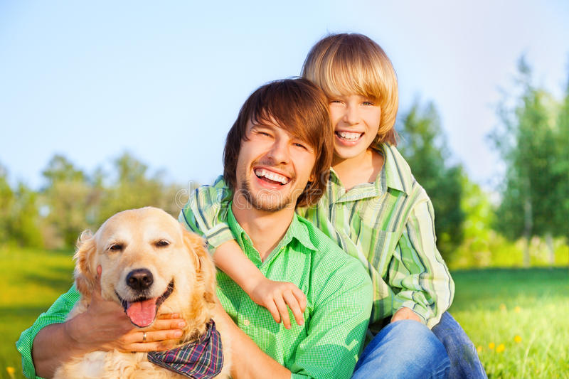 Smiling boy, father and dog sit in park on grass. In summer royalty free stock images