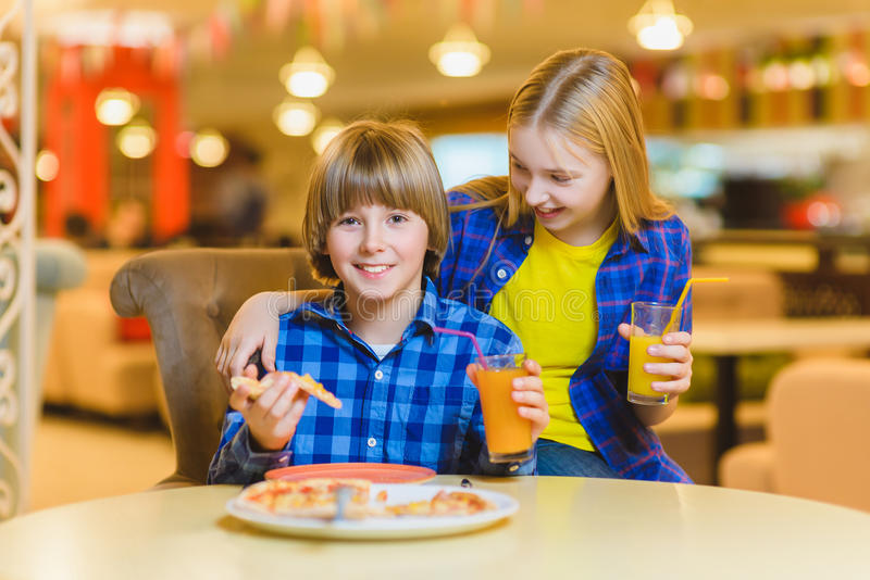 Smiling boy and girl eating pizza or drinking juice indoor royalty free stock photo