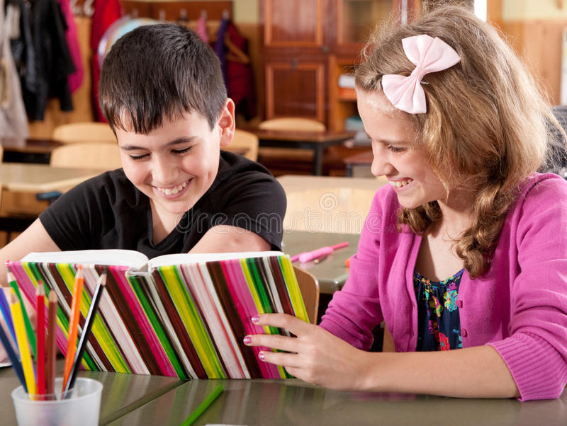 Smiling boy and girl reading book at school royalty free stock photography