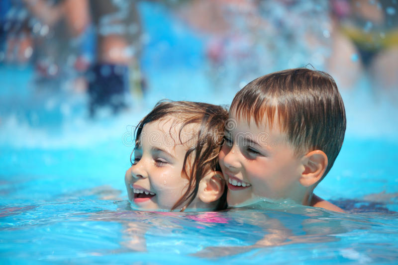 Smiling boy and girl swimming in pool in aquapark stock photo