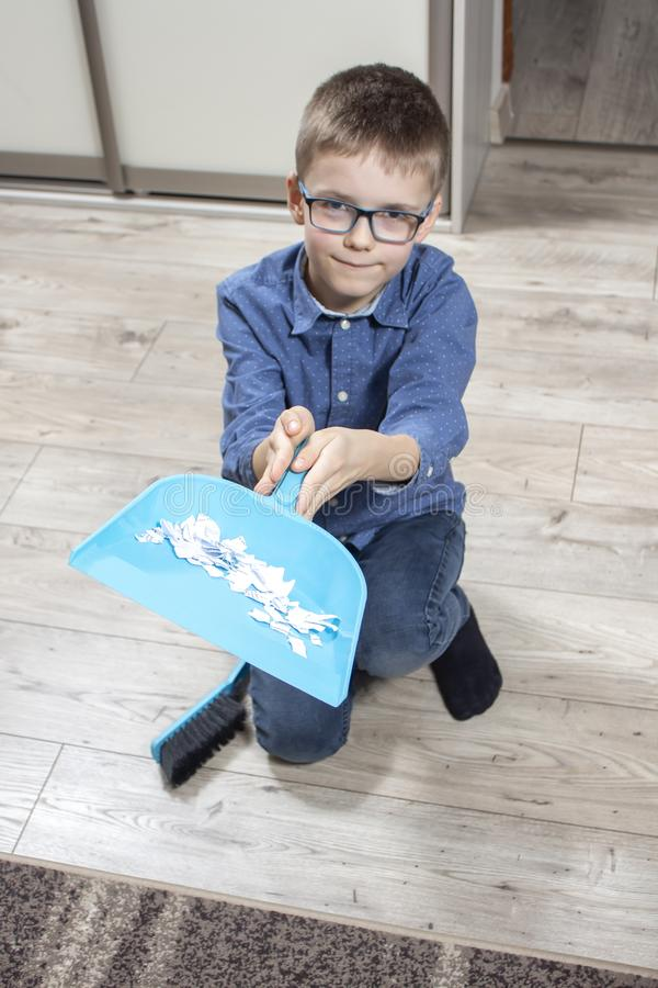 Smiling boy with glasses kneels on the floor and holds a scoop filled with papers. Boy in the glasses cleans the flat. He sweeps the paper on the scoop with a stock photos