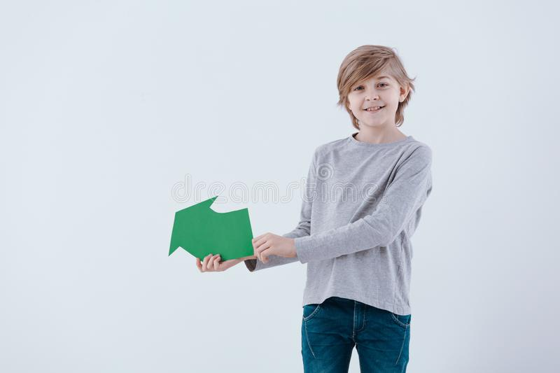 Smiling boy with green arrow royalty free stock images