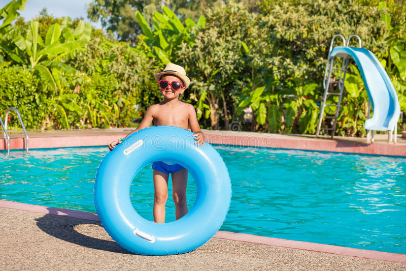 Smiling boy in hat holds blue inflatable ring. Smiling boy in hat and sunglasses holds blue inflatable ring standing near the swimming pool outside in summer stock images