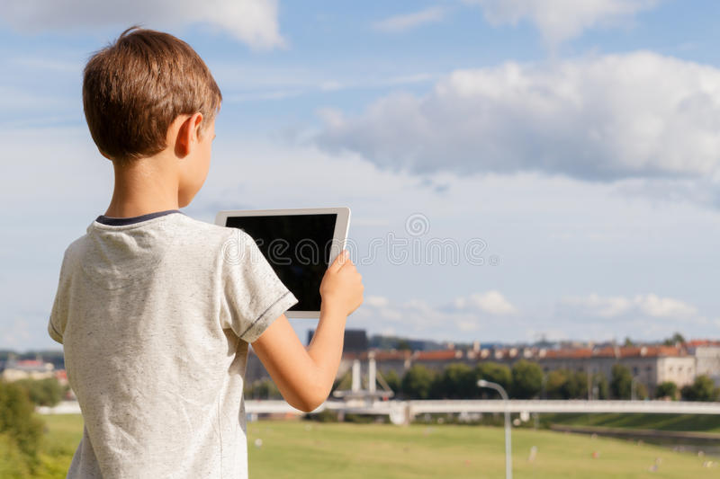 Smiling boy hold tablet PC. Outdoor. Blue sky and city background. Back to school, education, learning, technology royalty free stock images
