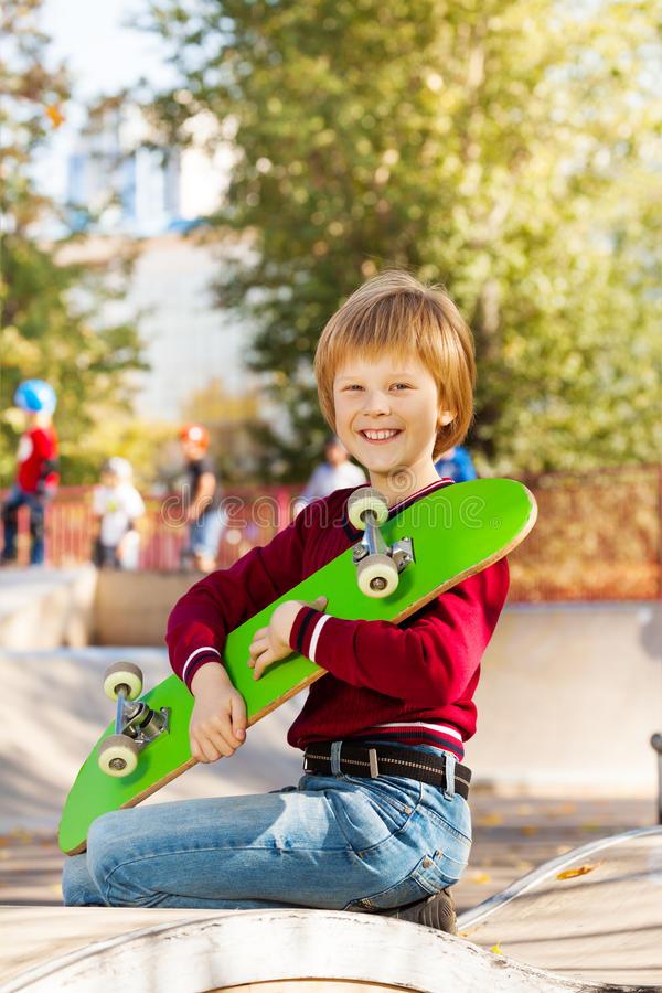 Smiling boy holding with arms green skateboard. Smiling boy holding with both arms green skateboard sitting on the children playground during autumn royalty free stock images