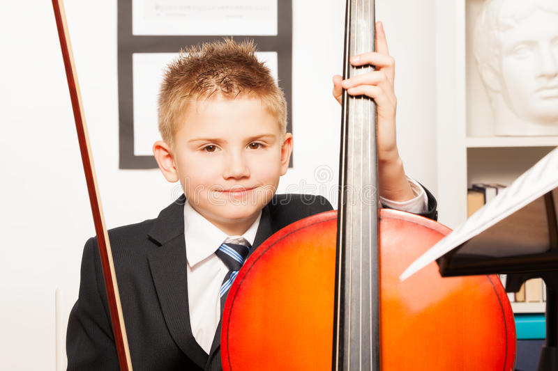 Smiling boy holding fiddlestick, play violoncello. Smiling boy holding the fiddlestick to play violoncello indoors stock images