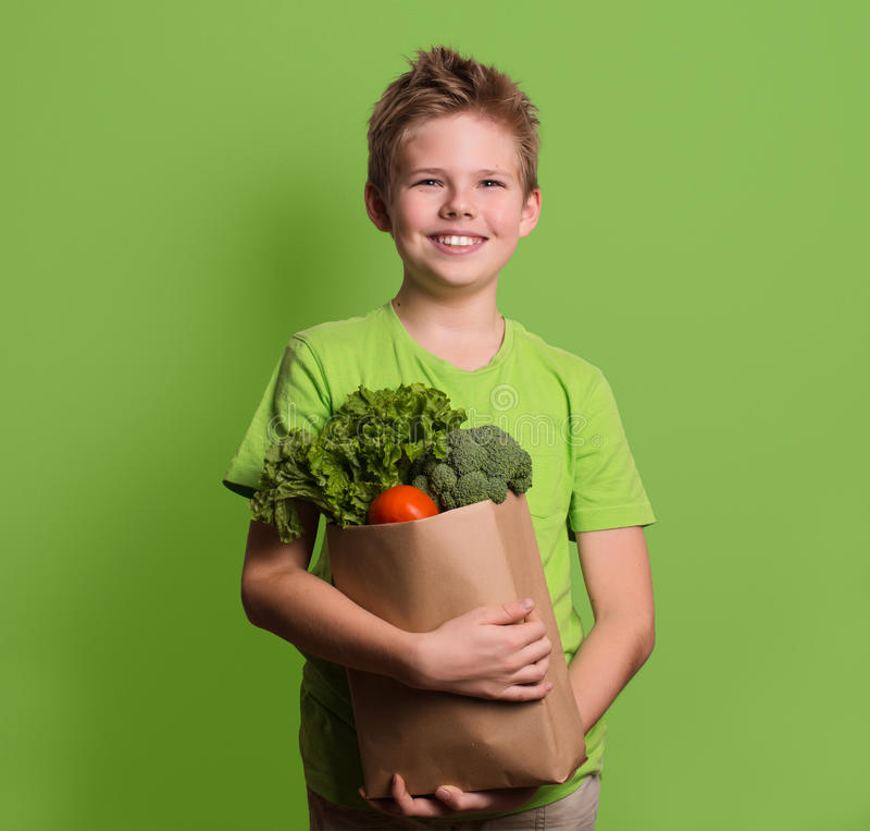 Smiling boy holding paper shopping bag full of fresh organic fru stock photography