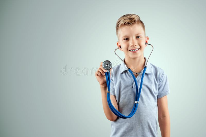 Smiling boy holding a stethoscope in his hands on an isolated light background. Medical education, choice of profession, future royalty free stock images
