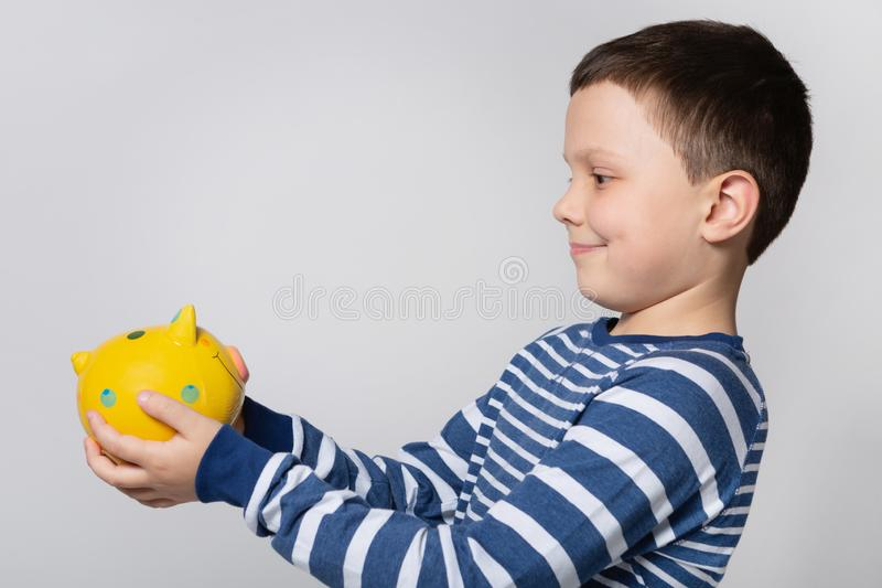Smiling boy holding a yellow piggy bank in front of him, looking at a piggy bank, concept of savings stock photos