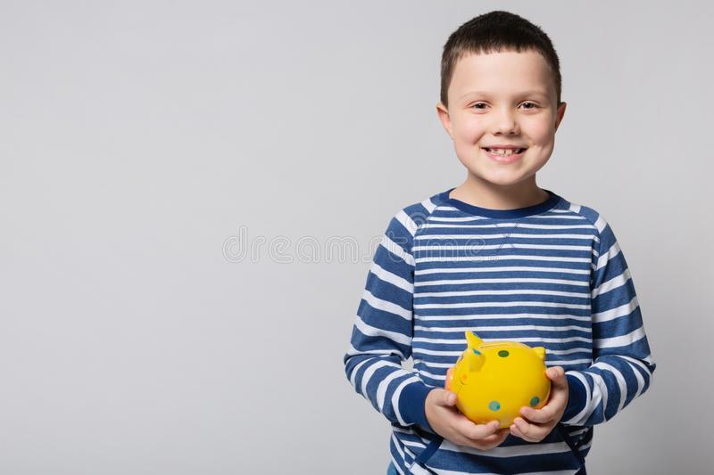 Smiling boy holding a yellow piggy bank in his hands, located frontally, the concept of savings and finance stock photo