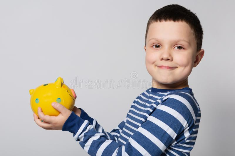 Smiling boy holding a yellow piggy bank in his hands, looking at the camera, concept of savings stock images