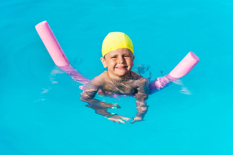 Smiling boy learns how to swim with pool noodle. In swimming pool during summer royalty free stock photography