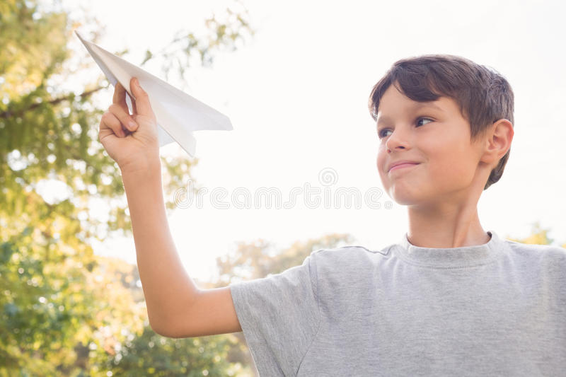 Smiling boy with paper plane in the park royalty free stock photos