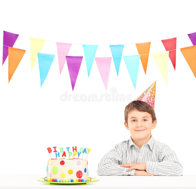 Smiling boy with party hat and a birthday cake. Isolated against white background stock photography