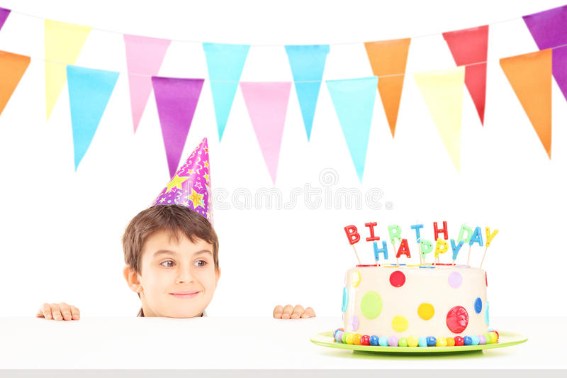 Smiling boy with party hat looking at a birthday cake. Isolated on white background royalty free stock photography