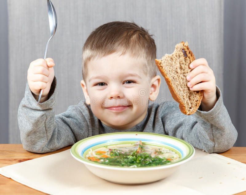 Smiling boy with plate of soup for dinner. At home royalty free stock photo