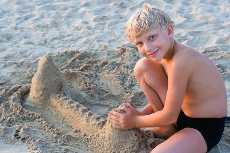 Smiling boy playing on sandy b royalty free stock photo