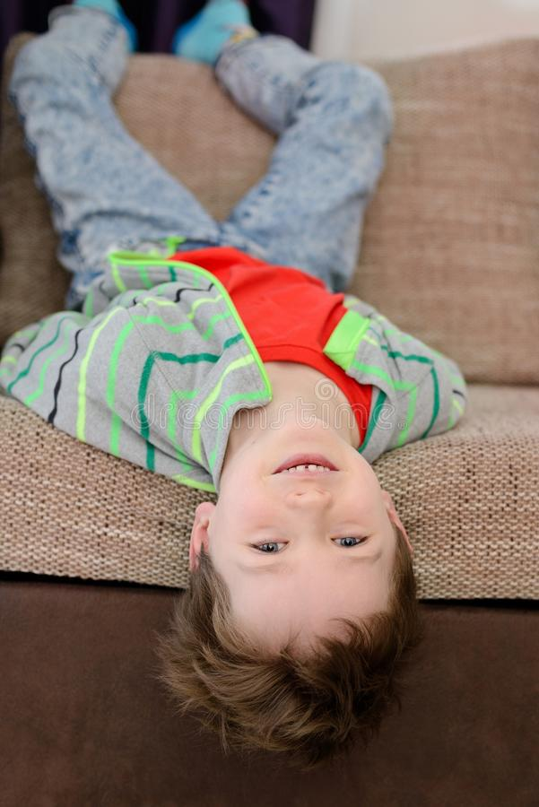 Smiling boy playing on the sofa stock image