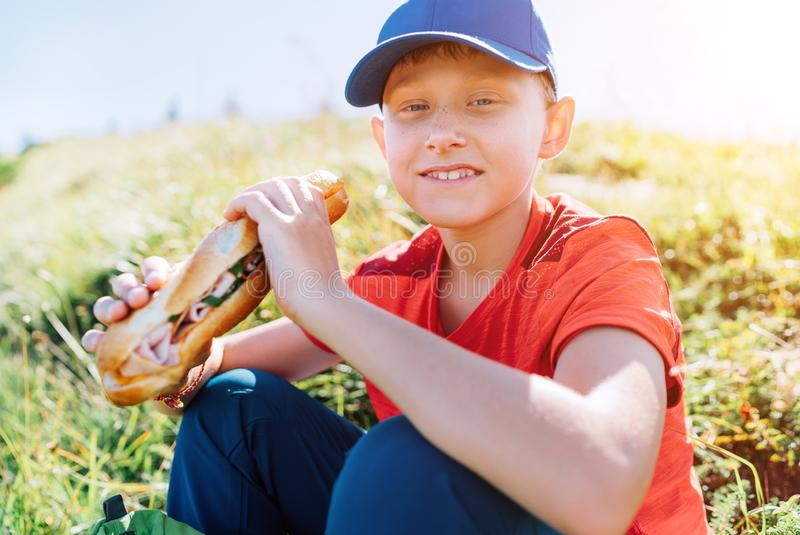 Smiling boy portrait with huge long baguette sandwich on the mountain path food break point royalty free stock images