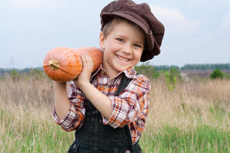 Smiling boy with pumpkin on his shoulder stock images