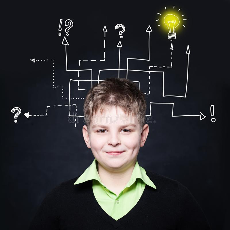 Smiling boy with question signs and light idea bulb stock photo