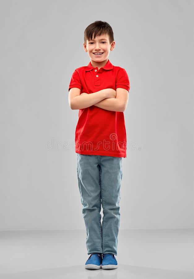 Smiling boy in red polo t-shirt with crossed arms. Childhood, expressions and people concept - smiling little boy in red polo t-shirt with crossed arms over grey royalty free stock photography
