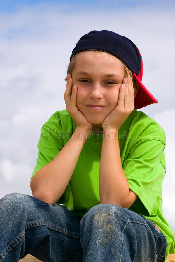 Smiling boy relaxing head in hands. Smiling boy head in hands wearing jeans, t-shirt and baseball cap sitting outside stock photography