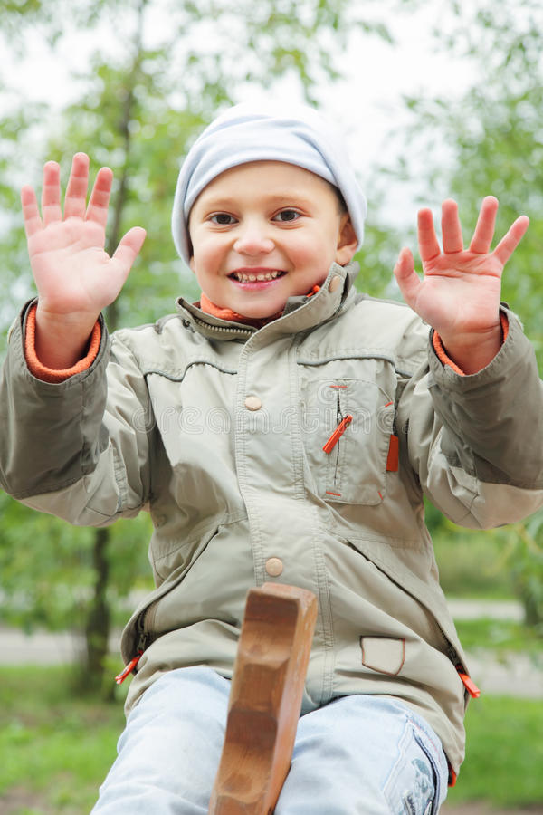 Download Smiling boy on seesaw stock photo. Image of jacket, positive - 15943348