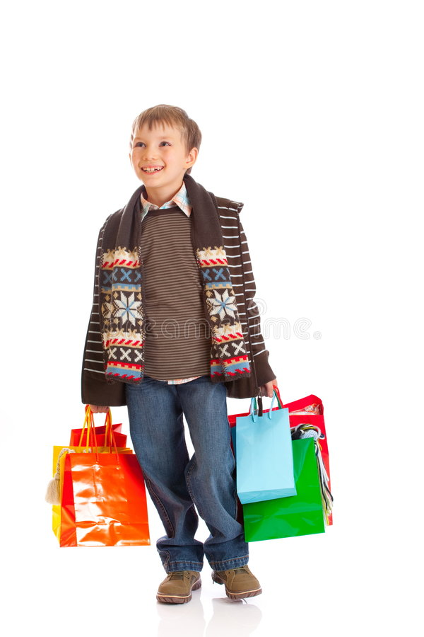 Smiling boy with shopping bags. Smiling young boy holding colorful shopping bags, isolated on white background royalty free stock photo