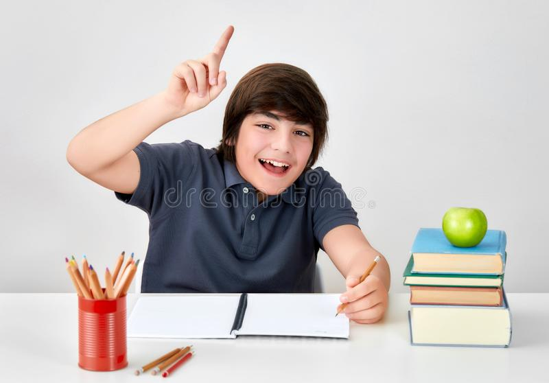 Smiling boy sitting at the desk raising hand with index finger to answer the question in the classroom. Smiling boy sitting at the desk raising hand with index stock images