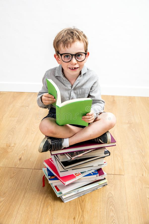Smiling boy sitting on pile of books for growing learning. Smiling 7-year old boy sitting on a pile of books for growing learning, curiosity and happy elementary stock photos