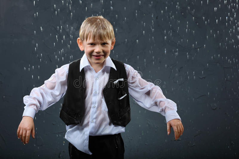 Download Smiling boy stands in rain stock image. Image of ragged - 22735933