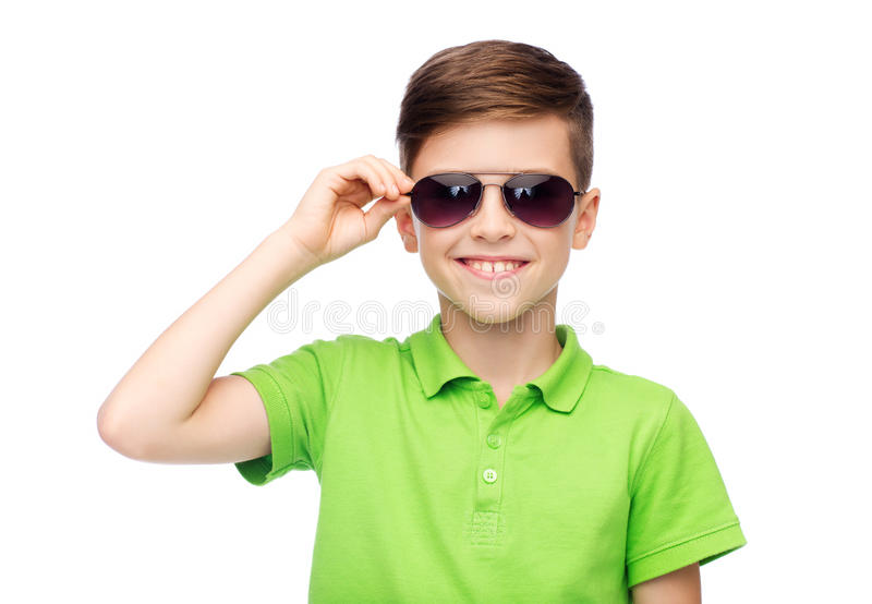 Smiling boy in sunglasses and green polo t-shirt. Childhood, fashion, accessory, style and people concept - happy smiling boy in sunglasses and green polo t stock photography