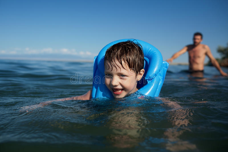 Smiling boy swimming. In the life jacket and the father stock photo