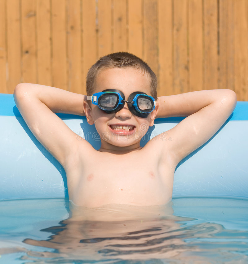 Smiling boy in swimming pool. Smiling 6 years old boy in swimming pool stock image