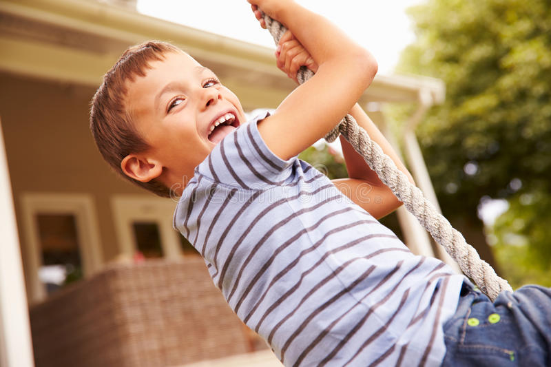 Smiling boy swinging on a rope at a playground stock photography