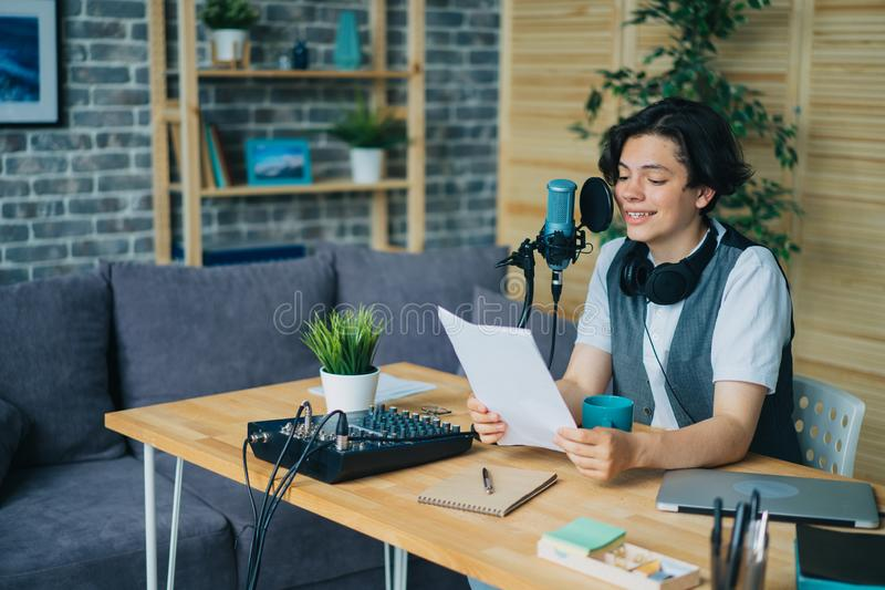 Smiling boy reading aloud in microphone recording podcast in modern studio. Smiling boy teenager is reading aloud in microphone recording podcast in modern stock photo