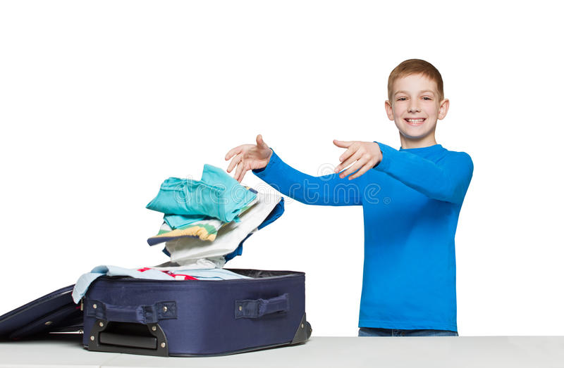 Smiling boy throwing clothes to luggage bag. Boy going travelling packing luggage bag with clothes stock images