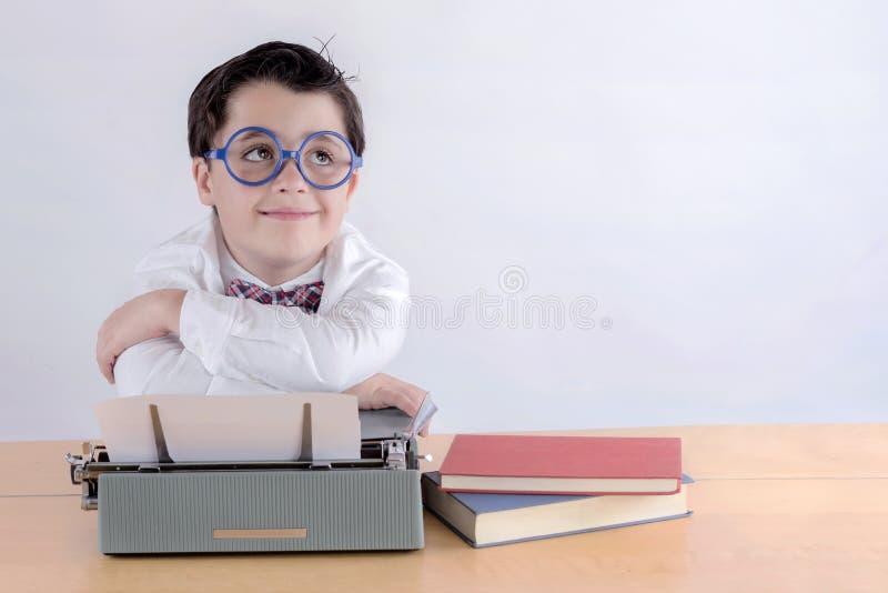 Smiling boy with typewriter. On white background stock photo