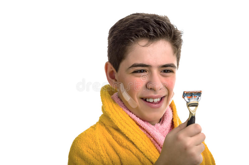 Smiling boy in yellow bathrobe and pink towel stares at the razor used for shaving. A Hispanic boy wears a yellow bathrobe with a pink towel around his neck: he royalty free stock image
