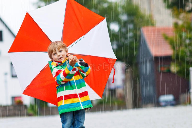 Smiling boy with yellow umbrella and colorful jacket outdoors at royalty free stock photography