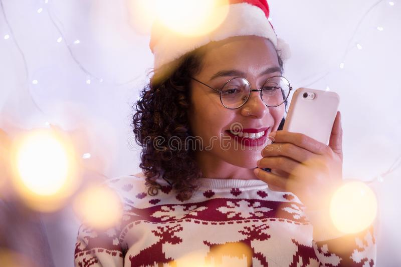 Brazilian girl wearing christmas hat and seasonal sweater checking social media in smartphone at home. decor blur lights. Smiling Brazilian girl wearing royalty free stock images