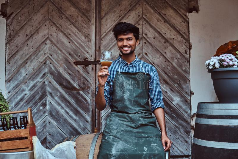 Brewmaster sitting on wooden barrel and holds a glass of craft beer relaxes after work. Smiling brewmaster sitting on wooden barrel and holds a glass of craft royalty free stock image