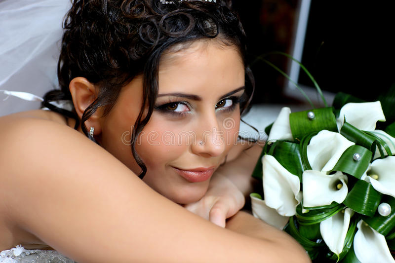 Smiling bride with bouquet of flowers. Bride with beautiful hairdo and bouquet of flowers stock image