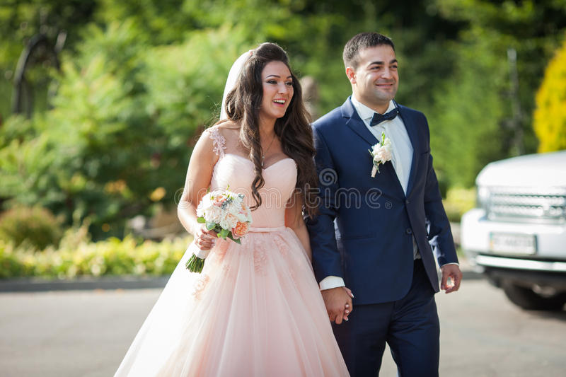Smiling bride with a bouquet and happy groom walking to the wedding aisle car in the background stock image